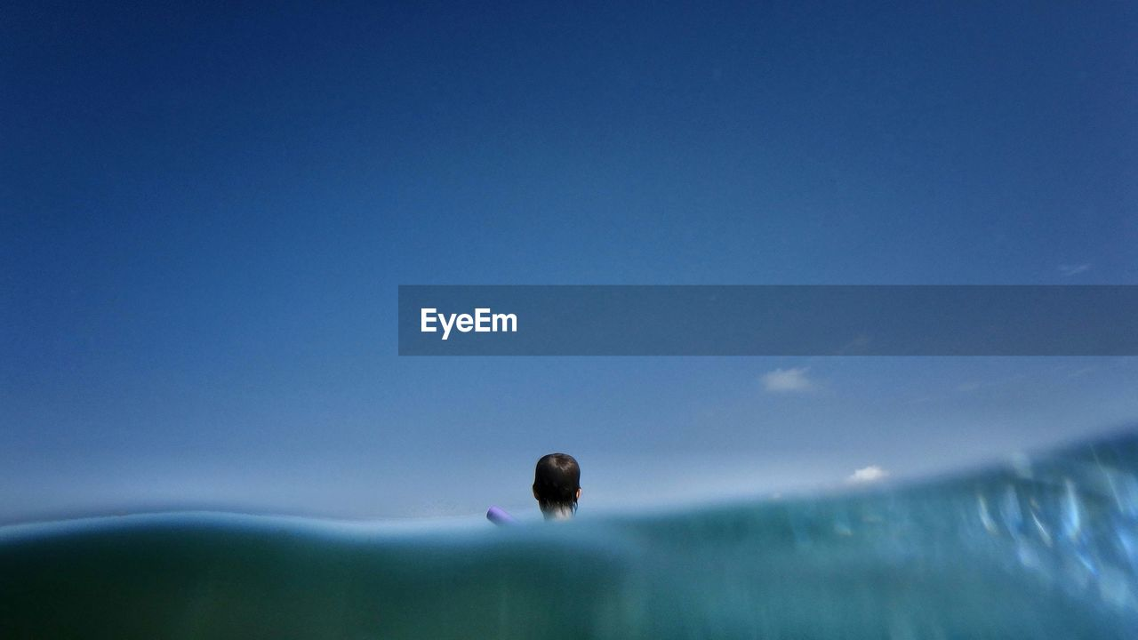Rear View Of Man Swimming In Sea Against Blue Sky