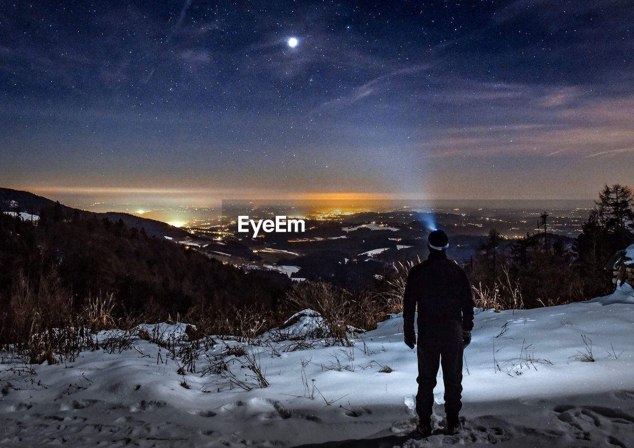 Rear View Of Man Standing On Snowcapped Mountain Against Star Field