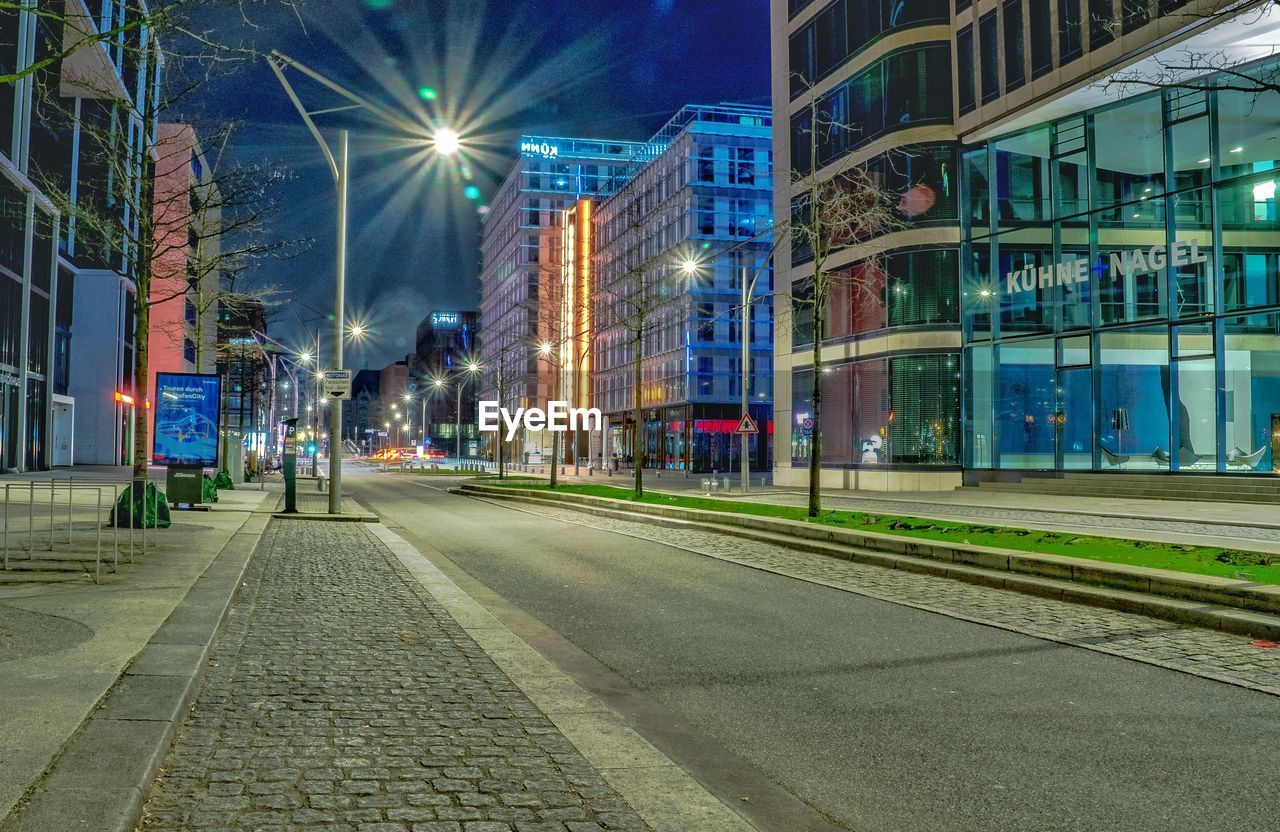 building exterior, architecture, built structure, illuminated, night, city, street, street light, transportation, rail transportation, building, railroad track, track, incidental people, road, city street, city life, outdoors, lighting equipment, office building exterior, light