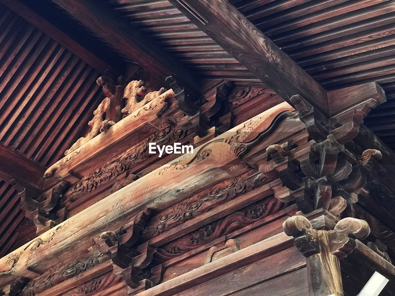 wood - material, indoors, low angle view, no people, built structure, religion, architecture, place of worship, belief, roof, ceiling, art and craft, spirituality, building, the past, history, creativity, large group of objects, craft, pattern, ornate, roof beam, carving, roof tile