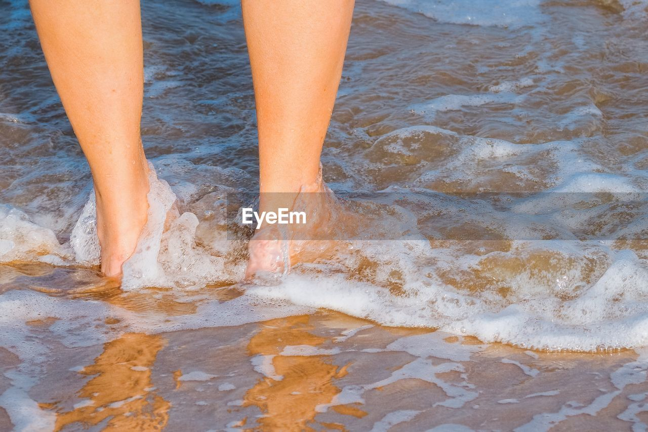 human body part, low section, human leg, body part, water, one person, land, real people, beach, lifestyles, barefoot, standing, women, high angle view, motion, leisure activity, sea, nature, outdoors, human limb, ankle deep in water, human foot