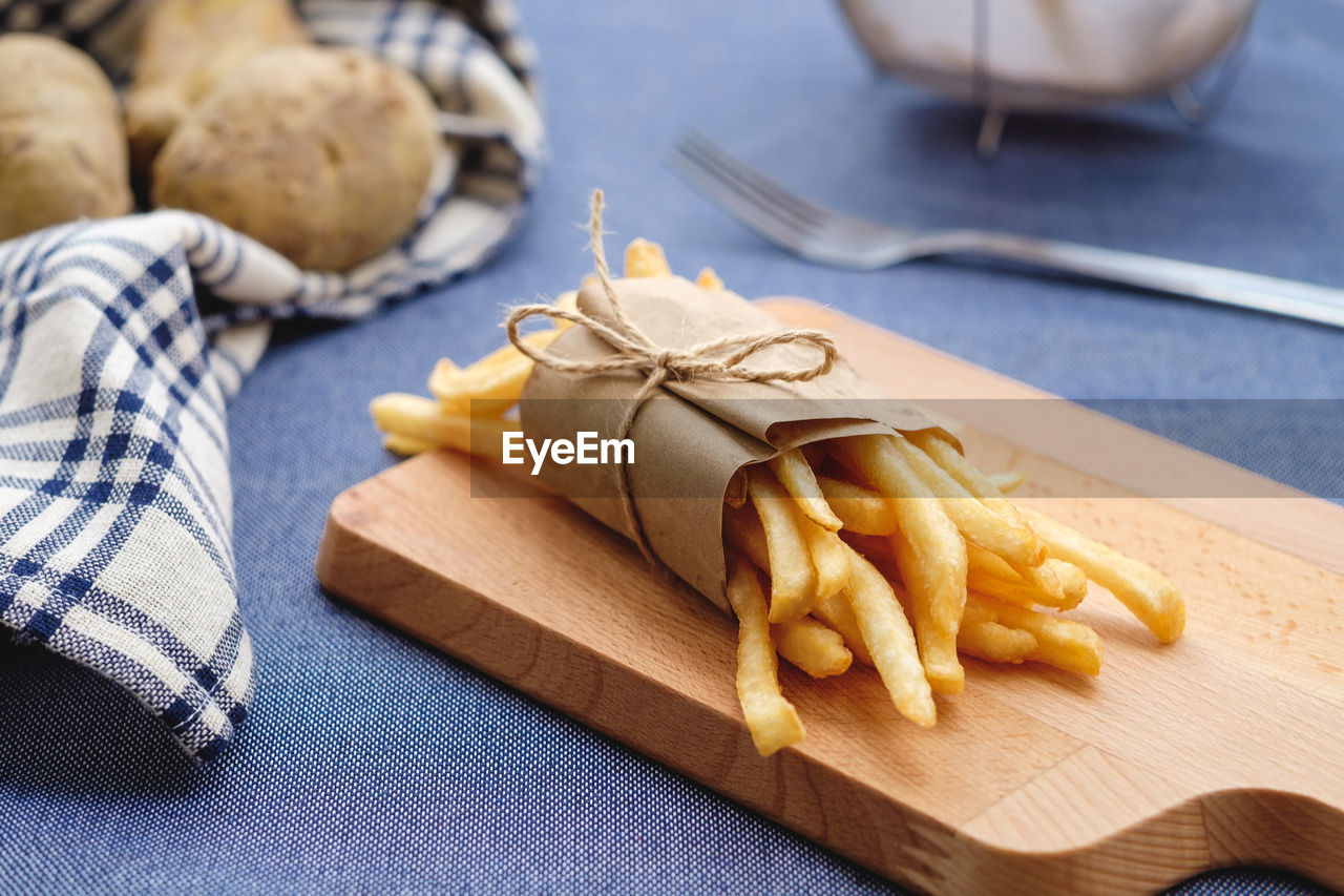Close-Up Of French Fries By Potatoes On Table