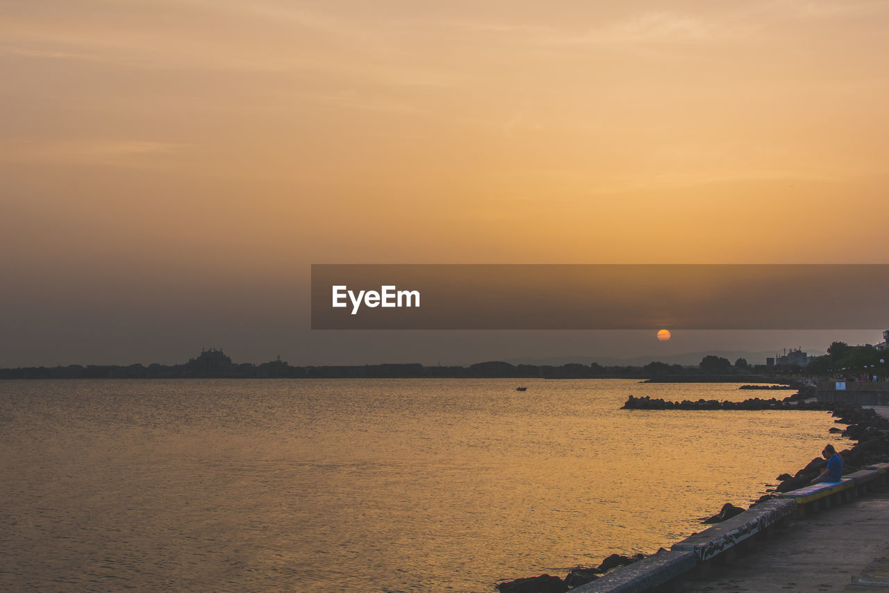 Scenic View Of Seascape Against Clear Sky During Sunset