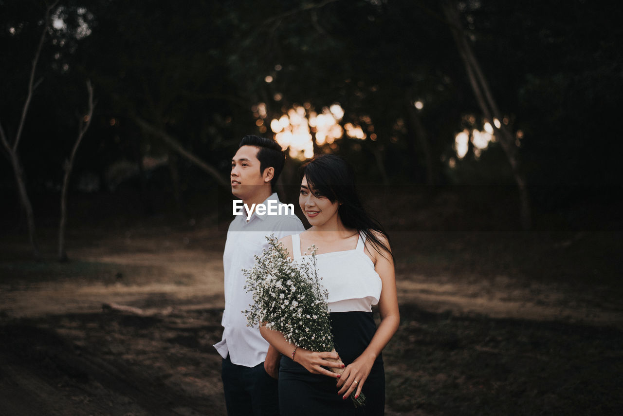 Smiling Young Woman With White Flowers Standing By Man