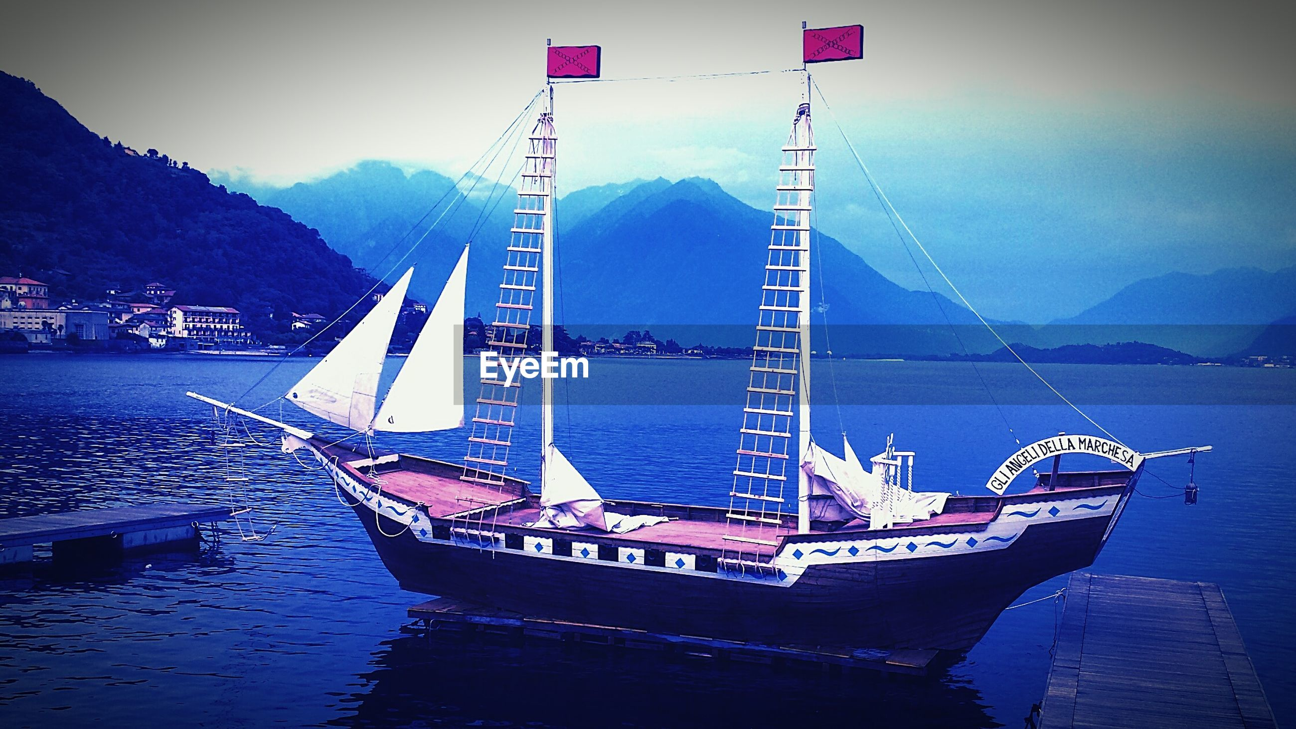 nautical vessel, transportation, water, boat, mode of transport, mountain, sky, waterfront, moored, river, sea, mast, mountain range, sailboat, connection, built structure, nature, outdoors, travel, harbor