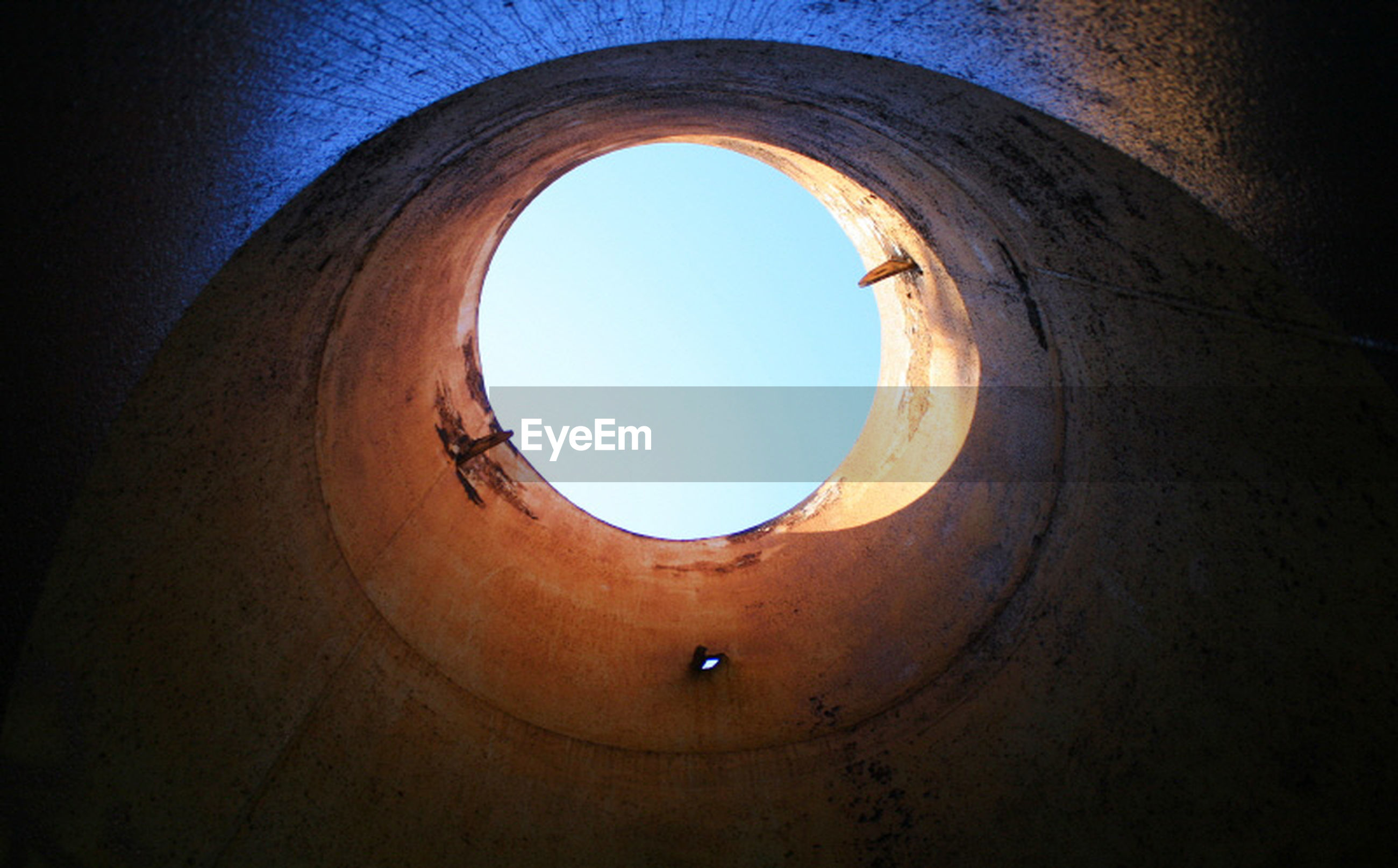 circle, indoors, architecture, low angle view, built structure, geometric shape, arch, copy space, clear sky, directly below, tunnel, sky, shape, no people, curve, hole, pattern, day, window, ceiling