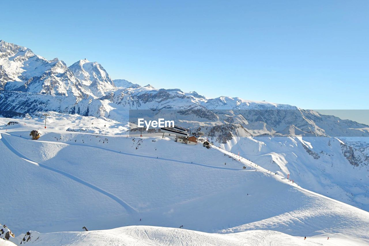snow, winter, mountain, cold temperature, nature, white color, scenics, beauty in nature, tranquil scene, blue, mountain range, outdoors, snowcapped mountain, weather, skiing, day, sunlight, landscape, tranquility, ski holiday, frozen, clear sky, vacations, sport, no people, sky, extreme sports, ski lift