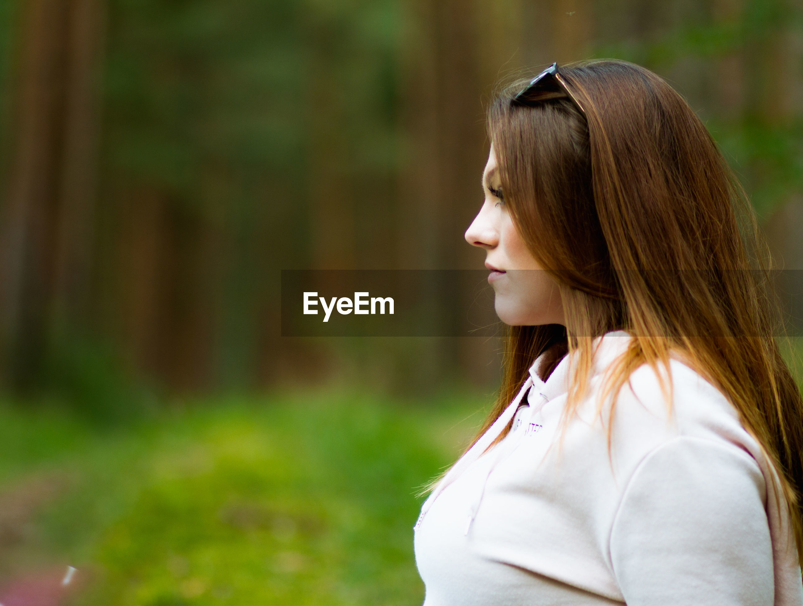 Side view of young woman looking away while standing against trees