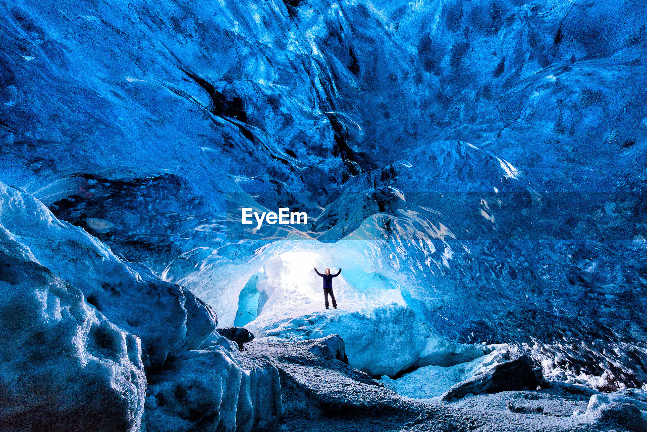 Excited person standing in ice cave