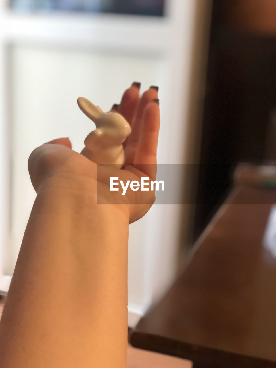 human hand, hand, human body part, indoors, real people, body part, one person, focus on foreground, lifestyles, human finger, finger, adult, home interior, close-up, women, personal perspective, holding, selective focus, leisure activity, care, human limb