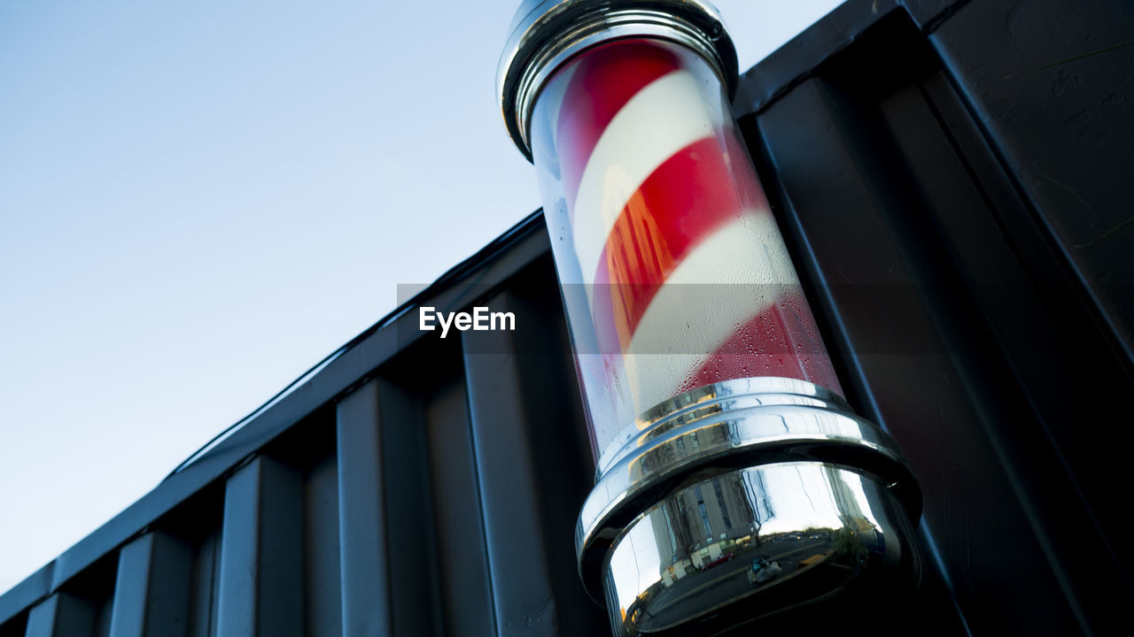 Low Angle View Of Barbers Pole On Container Against Clear Sky