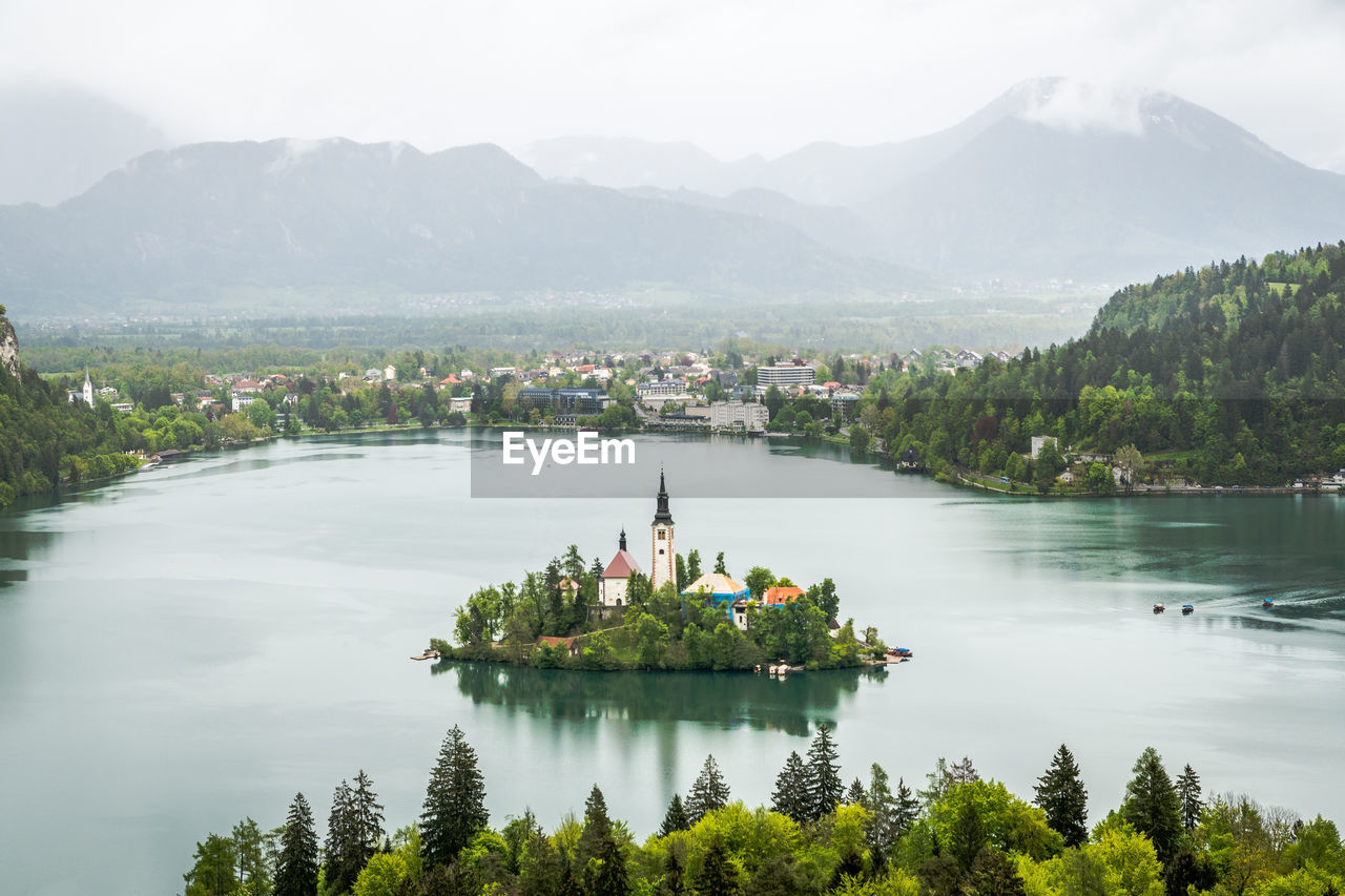 water, mountain, lake, tree, scenics - nature, beauty in nature, sky, waterfront, nature, day, plant, real people, group of people, transportation, tranquil scene, mountain range, architecture, nautical vessel, outdoors