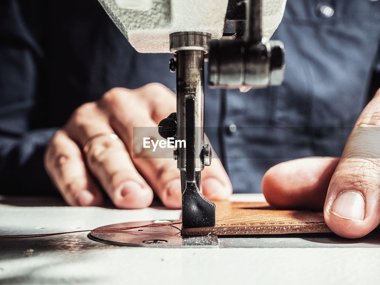 Close-Up Of Tailor Working On Sewing Machine