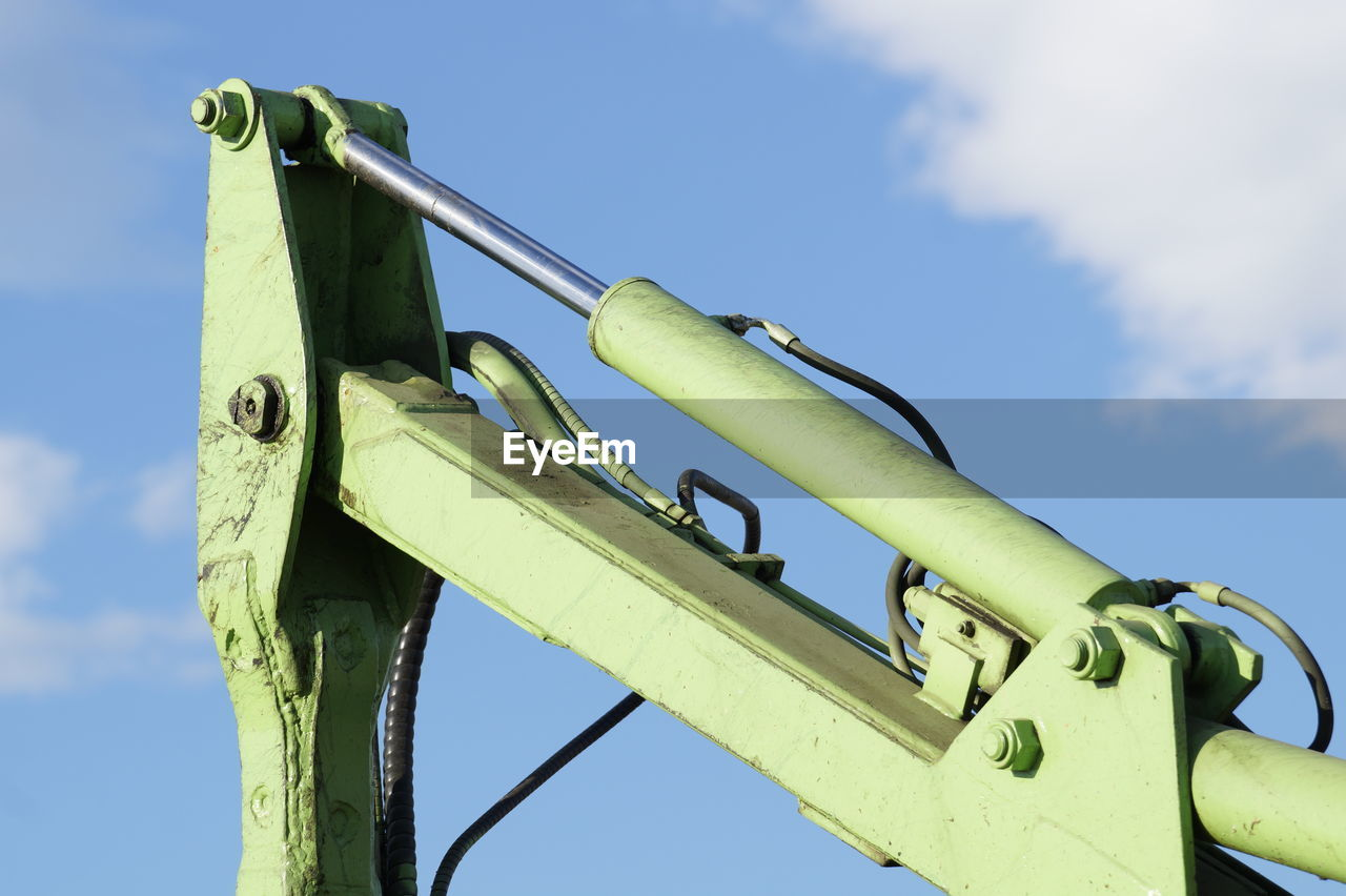 Low angle view of machinery against blue sky