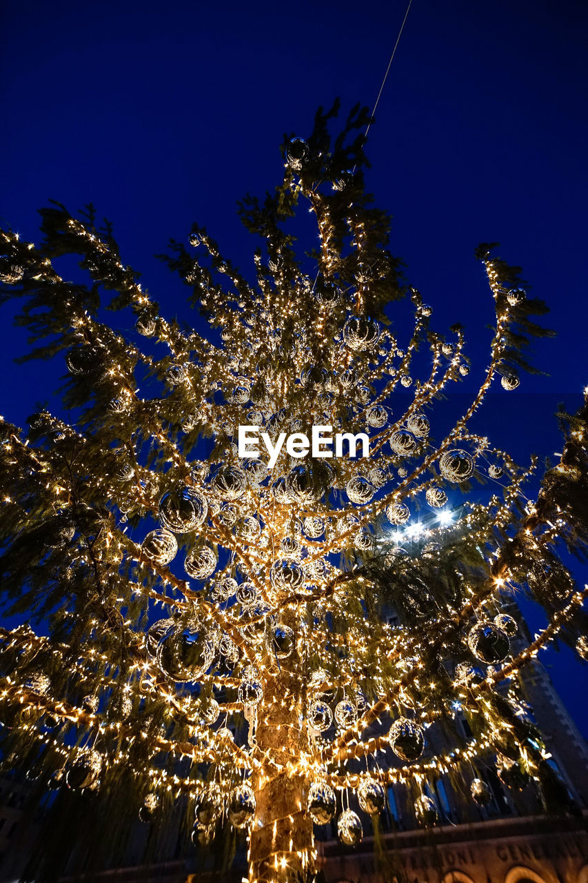 LOW ANGLE VIEW OF ILLUMINATED CHRISTMAS TREE AGAINST CLEAR SKY