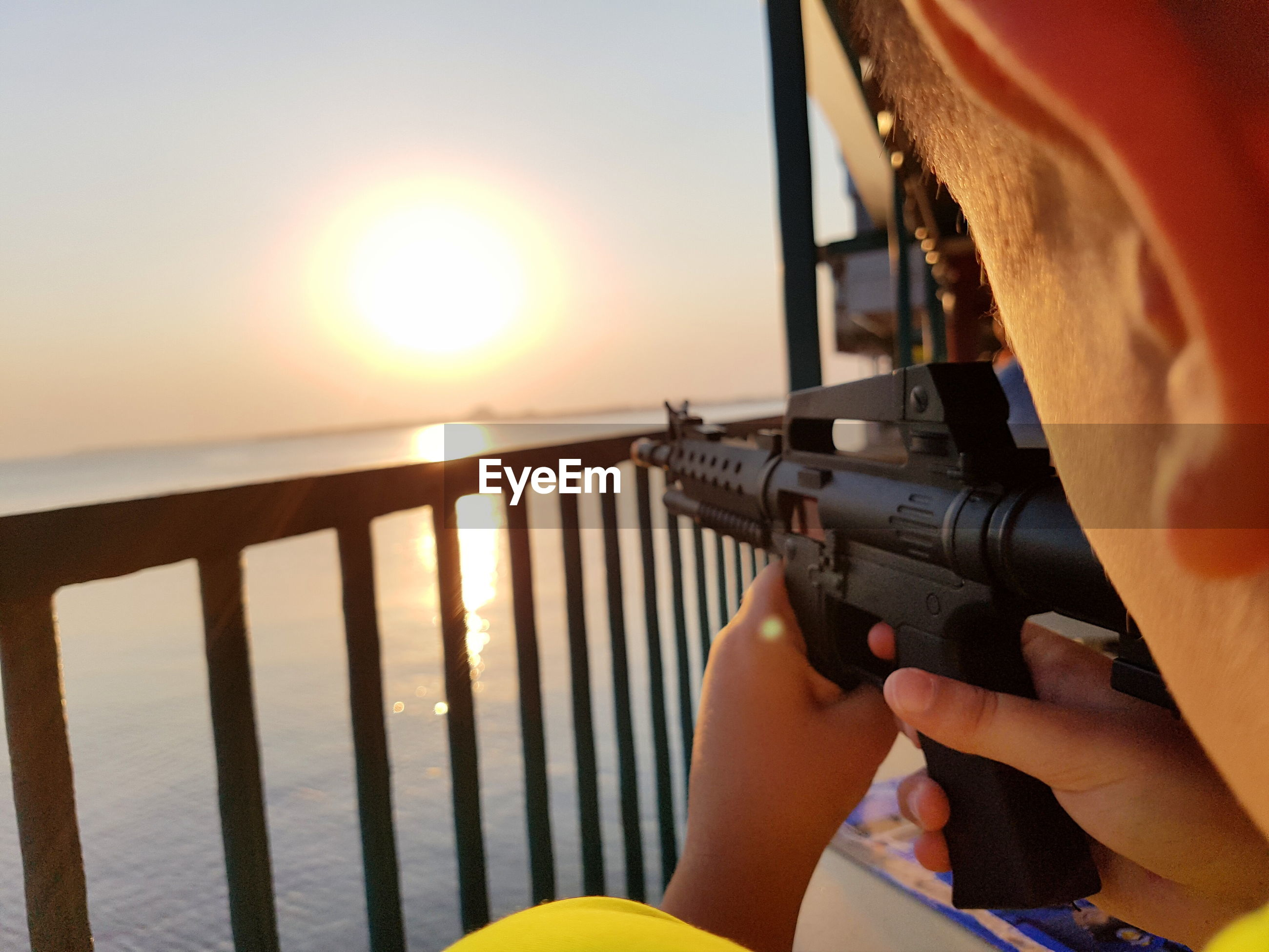 Midsection of boy holding rifle against sea during sunset