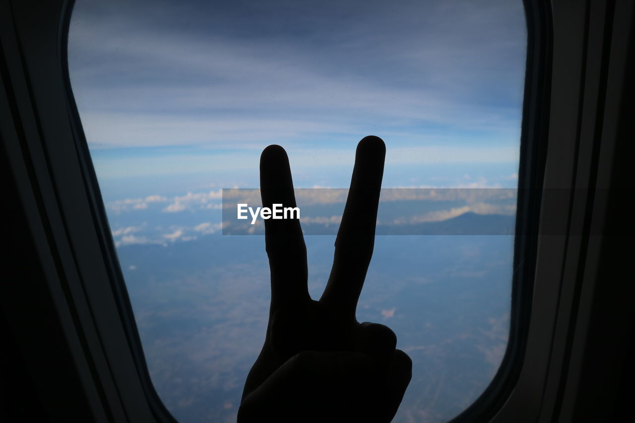 Close-up of person hand gesturing against airplane window