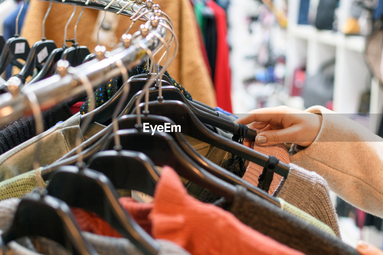 Cropped hand of woman shopping in clothing store