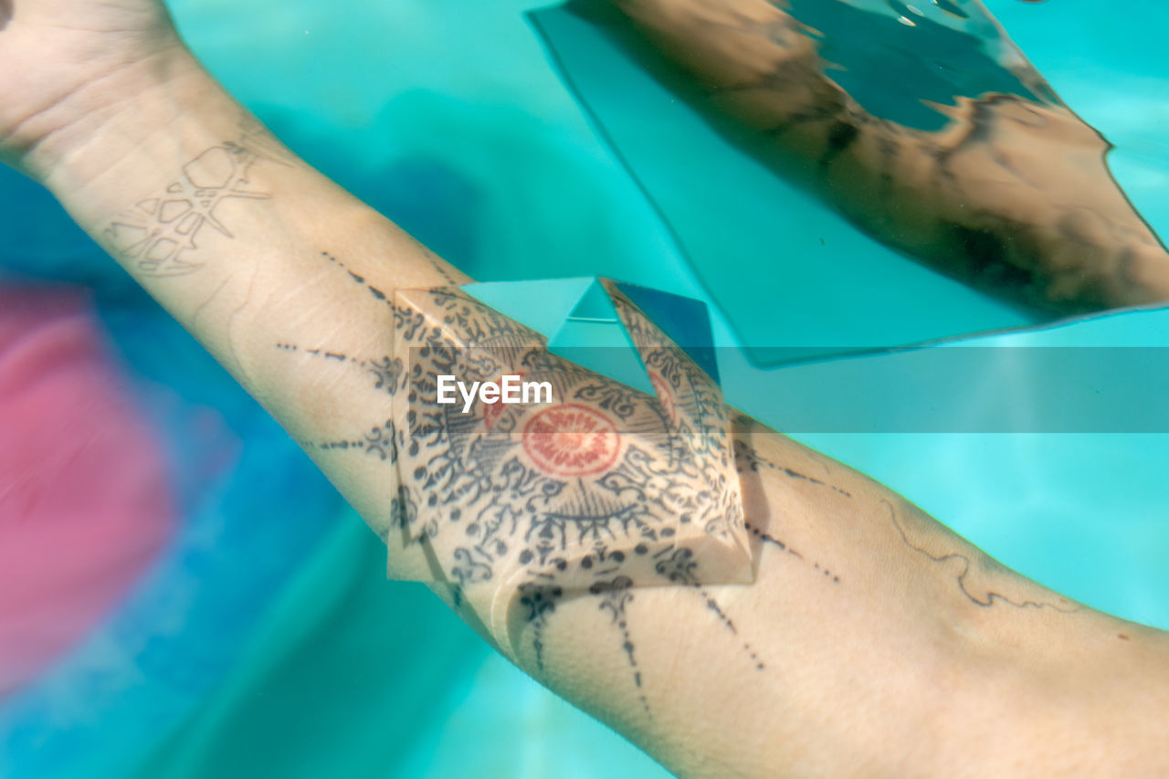 Cropped image of woman with prism on tattoo underwater
