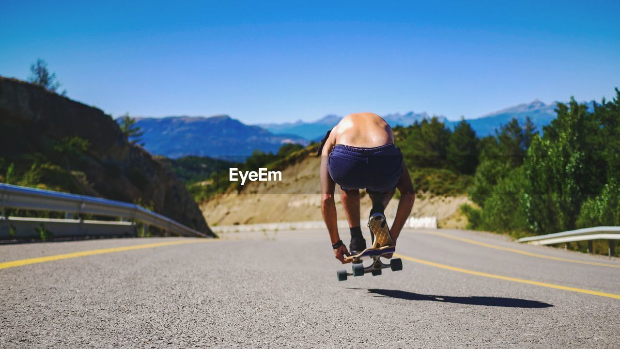 Rear View Of Man Skateboarding On Road Against Sky