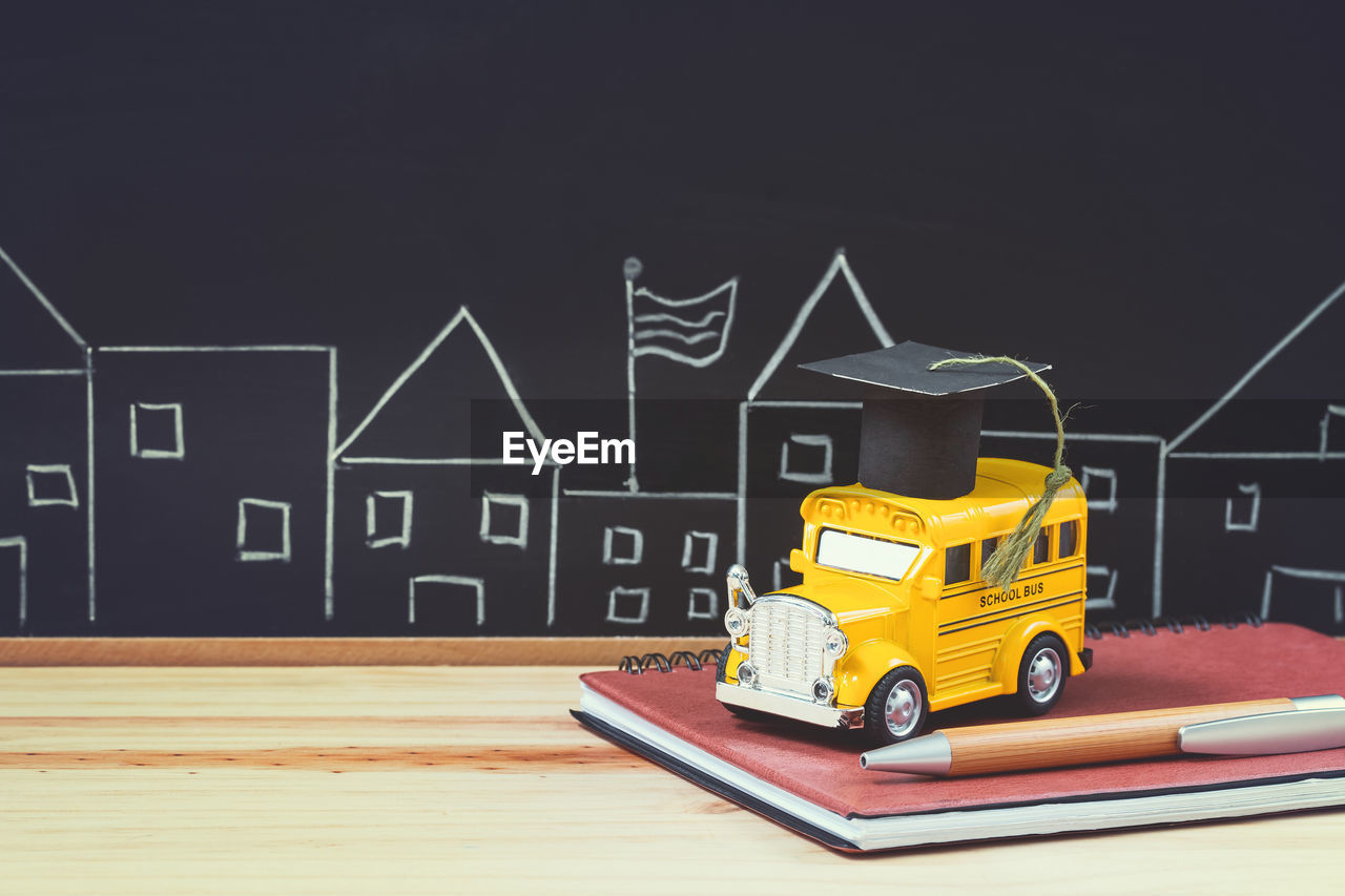 text, western script, no people, car, mode of transportation, architecture, motor vehicle, transportation, indoors, art and craft, communication, capital letter, toy, creativity, yellow, house, land vehicle, blackboard, building