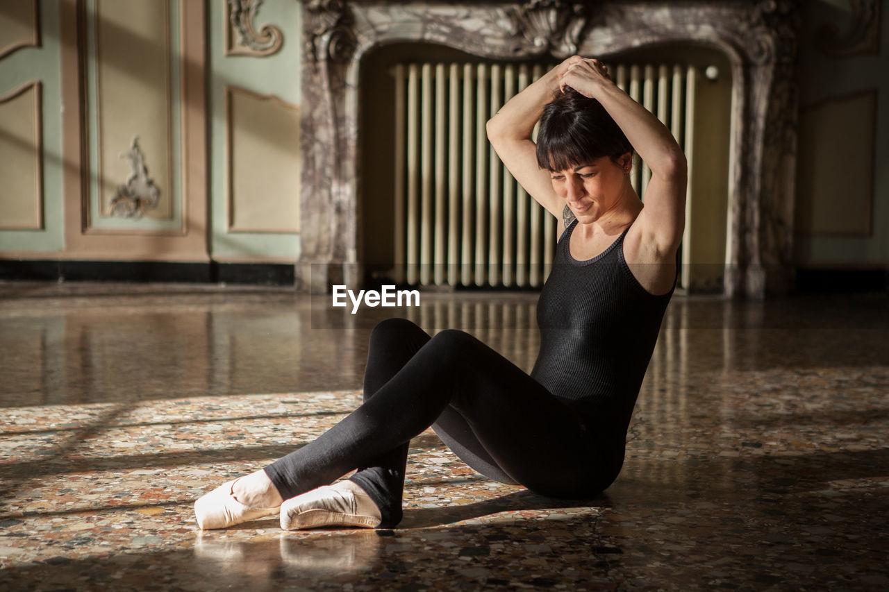 Ballerina Tying Hair Bun In Studio