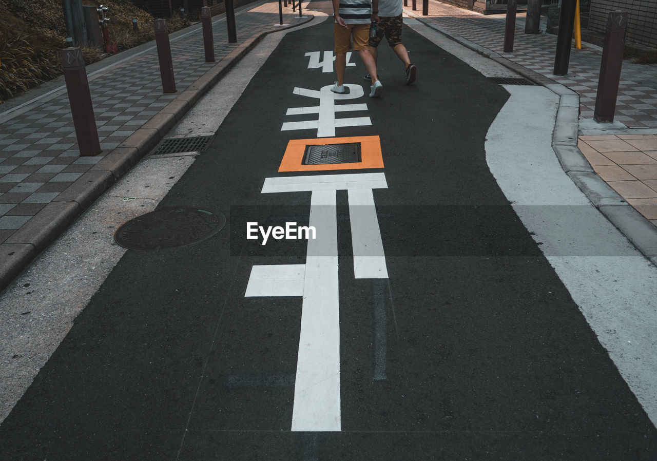 Low section of people walking on footpath with markings