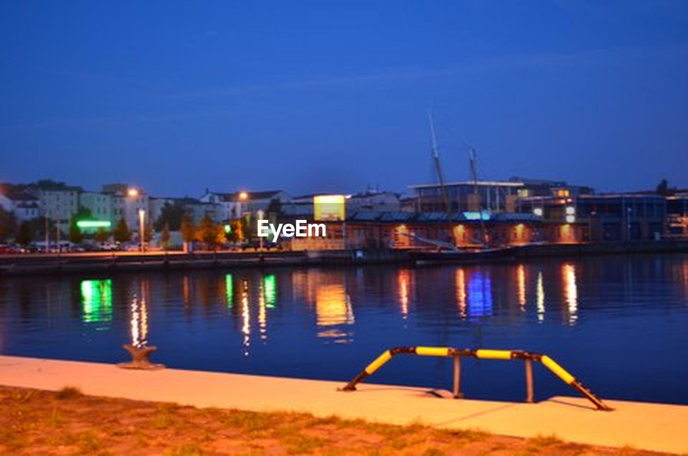 water, illuminated, built structure, architecture, night, building exterior, clear sky, reflection, river, blue, city, copy space, waterfront, outdoors, transportation, lake, no people, pier, sky, dusk