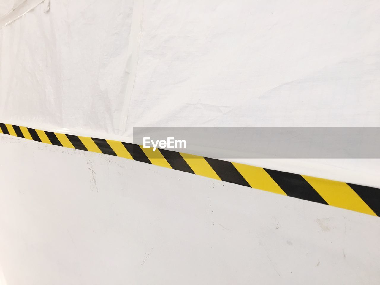 yellow, white color, no people, transportation, striped, day, high angle view, sign, architecture, mode of transportation, close-up, wall - building feature, outdoors, communication, pattern, full frame, nature, built structure, copy space, black color