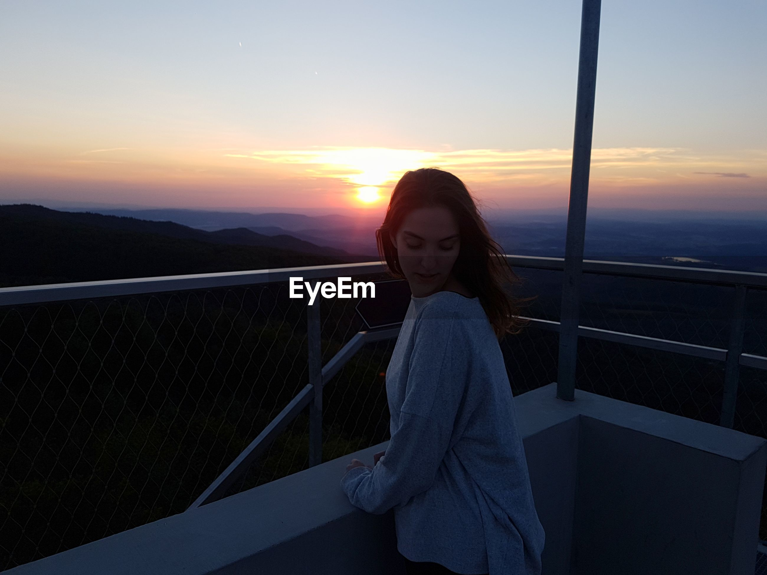 Portrait of young woman standing in balcony against sky during sunset