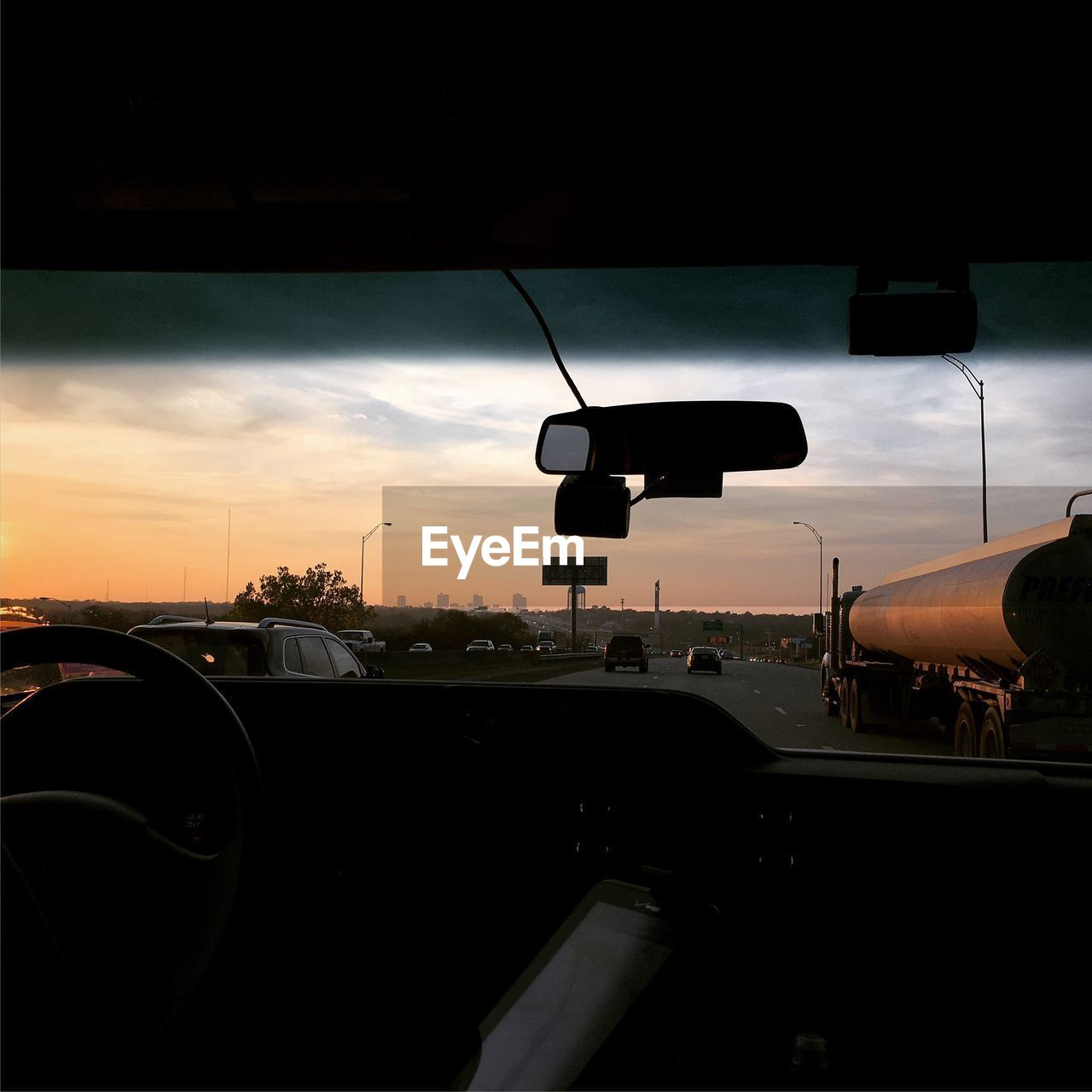 mode of transportation, transportation, car, land vehicle, cloud - sky, sunset, sky, motor vehicle, rear-view mirror, vehicle interior, windshield, orange color, indoors, travel, glass - material, no people, nature, road, transparent, city