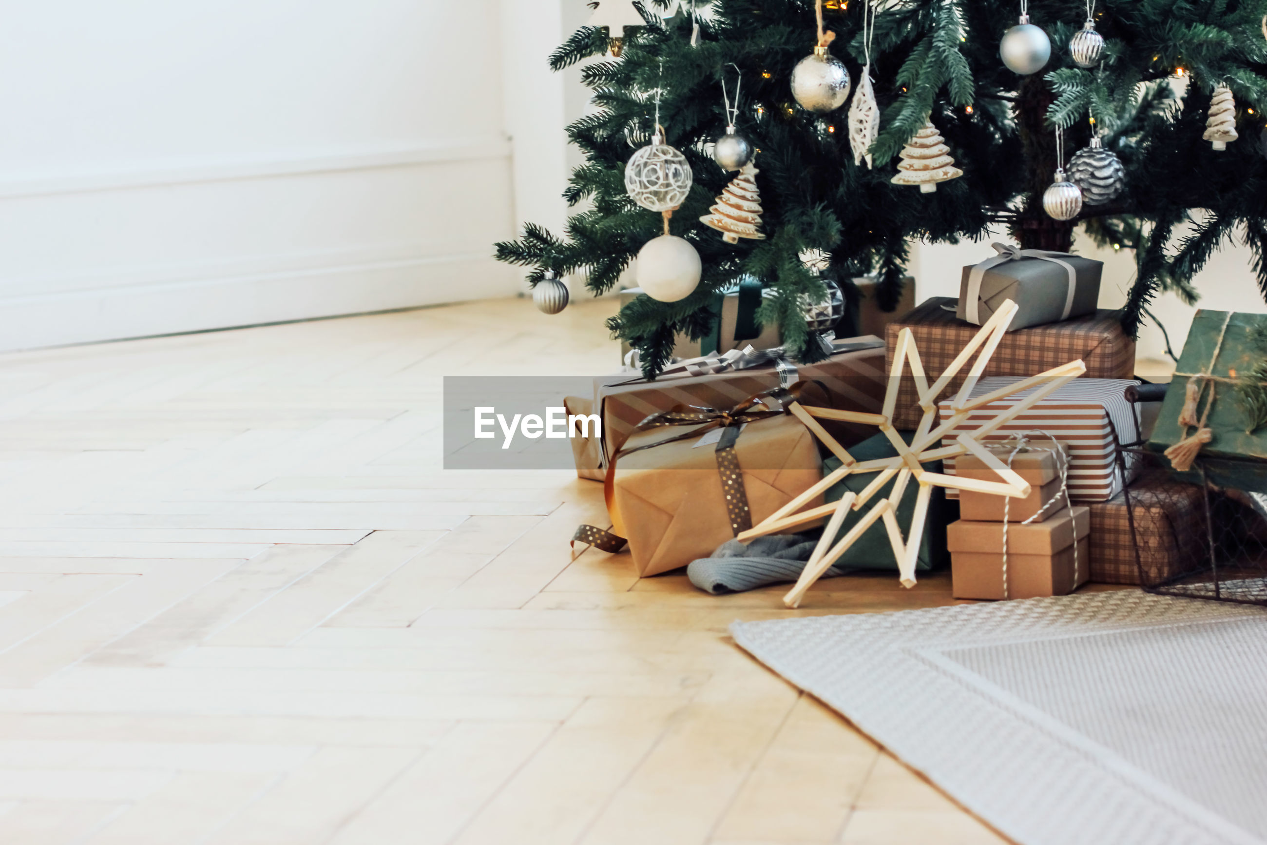 Christmas tree by gifts on hardwood floor at home
