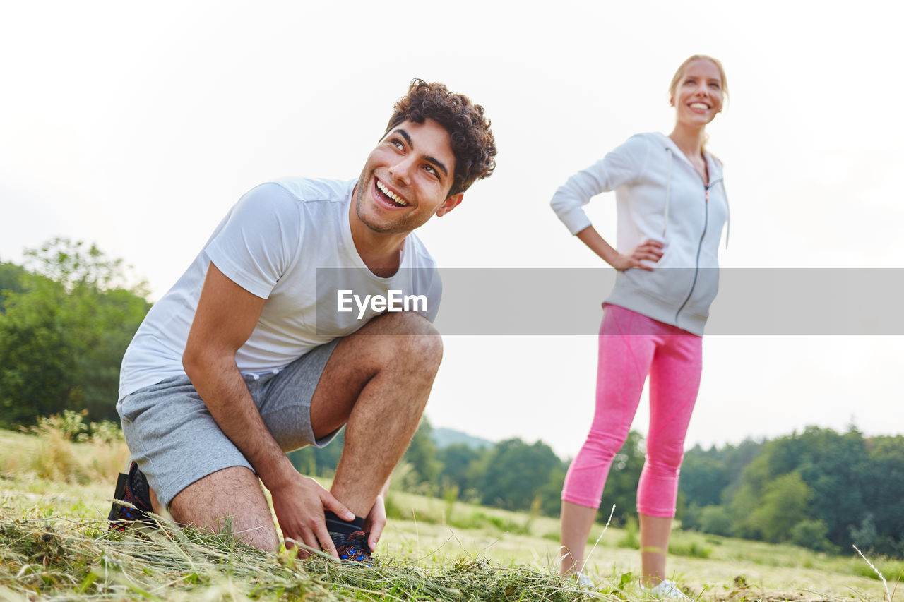 smiling, emotion, happiness, lifestyles, casual clothing, real people, two people, young adult, young men, leisure activity, looking at camera, togetherness, men, full length, portrait, people, standing, sky, adult, couple - relationship, positive emotion