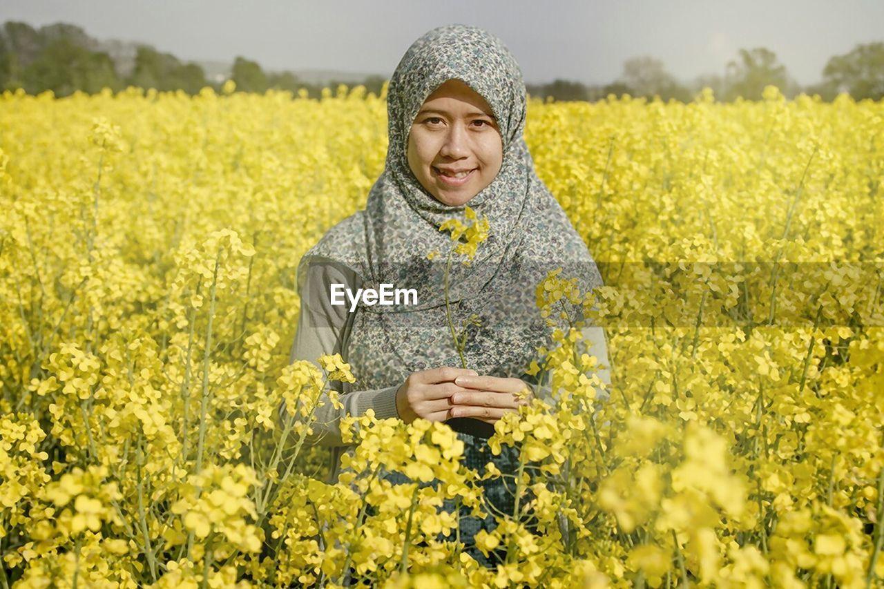 Portrait On Smiling Woman Standing On Oilseed Rape Field