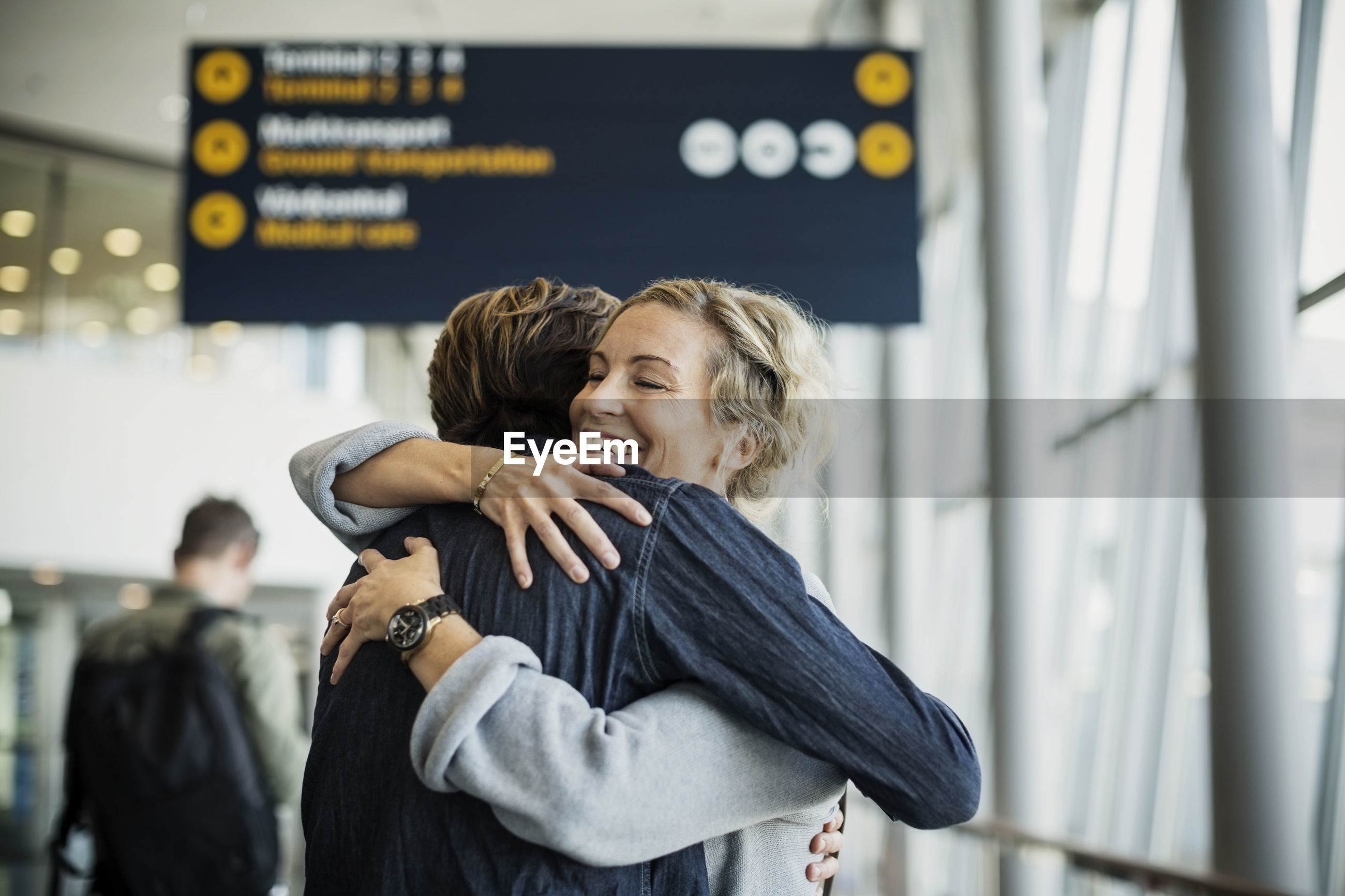 Happy businesswoman embracing male colleague at airport