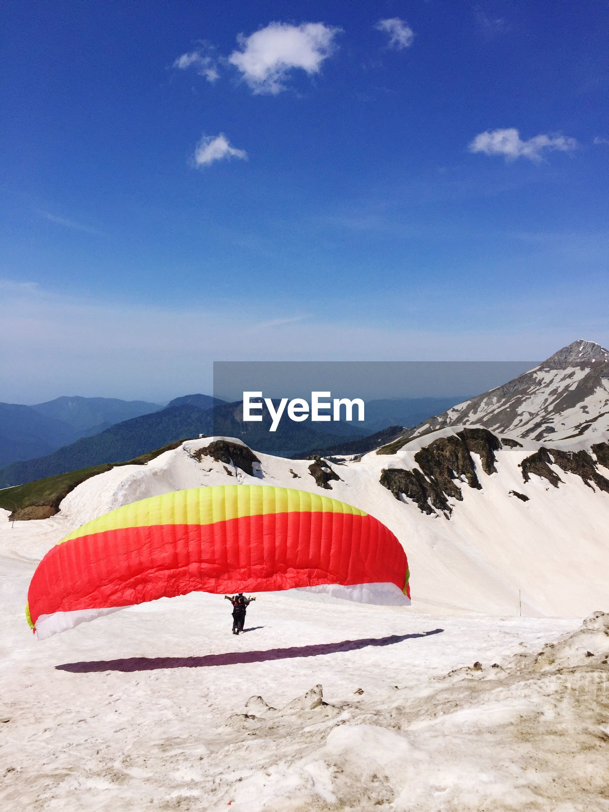 Man paragliding on scenic snowcapped mountains against blue sky