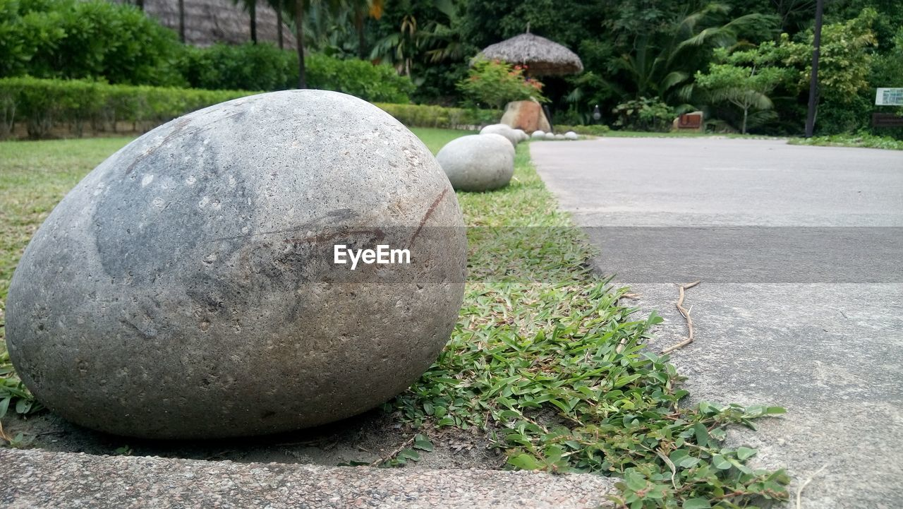 day, stone material, topiary, outdoors, sculpture, statue, grass, tree, ball, water, one person, architecture, nature, close-up, animal themes, people