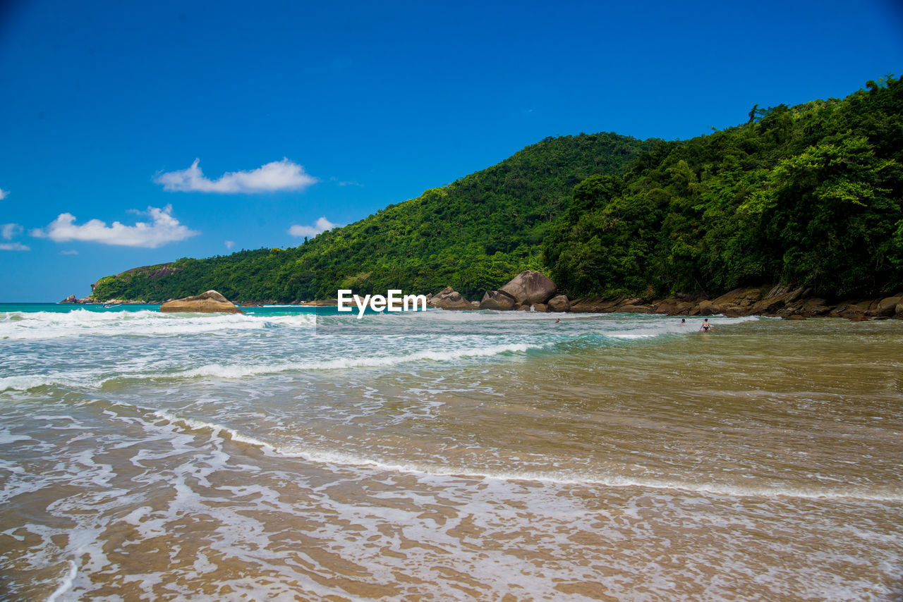 water, sea, sky, land, beach, beauty in nature, scenics - nature, tranquility, tranquil scene, nature, mountain, wave, motion, day, sport, no people, idyllic, tree, blue, outdoors, flowing water