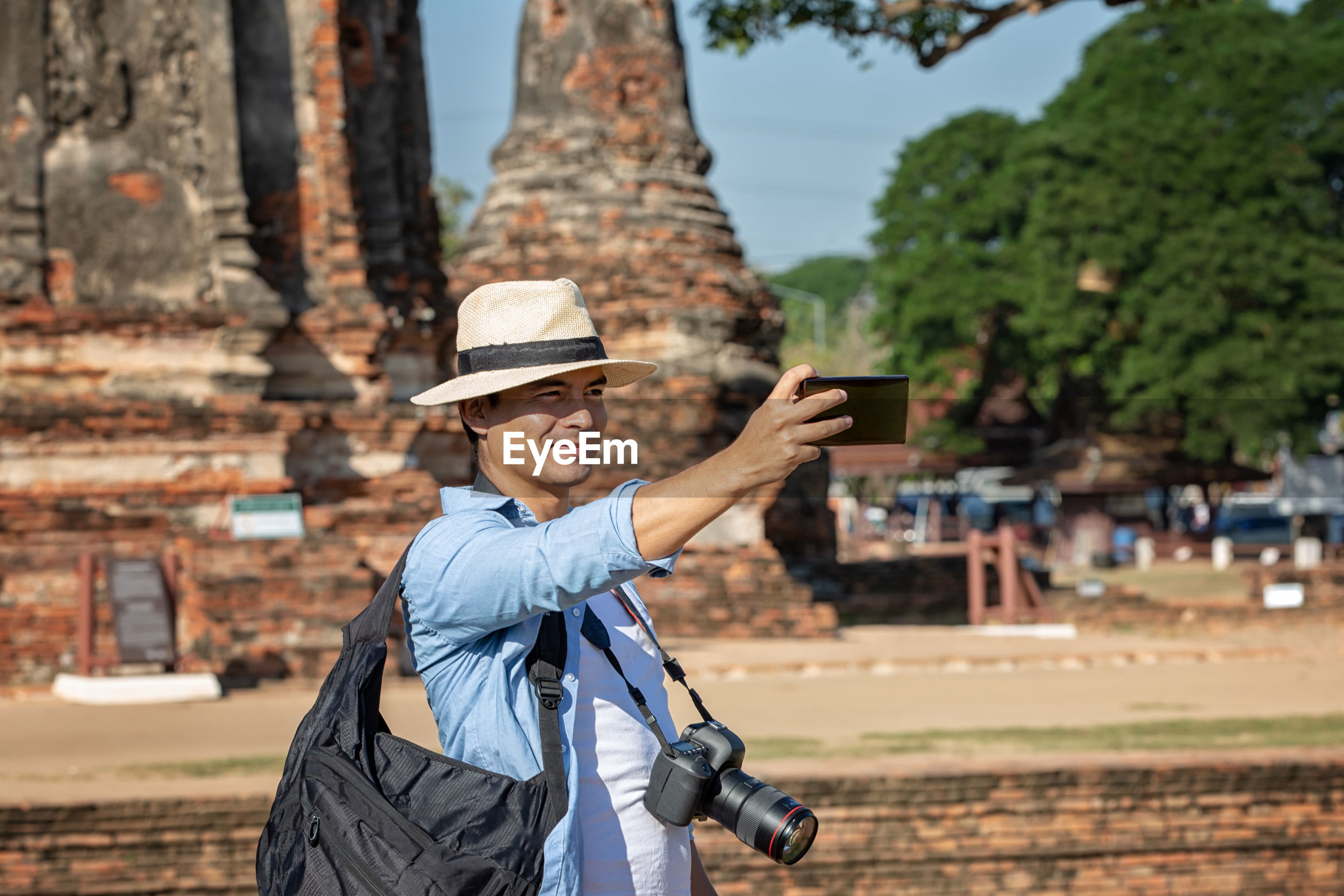 Smiling man taking selfie while standing against temple