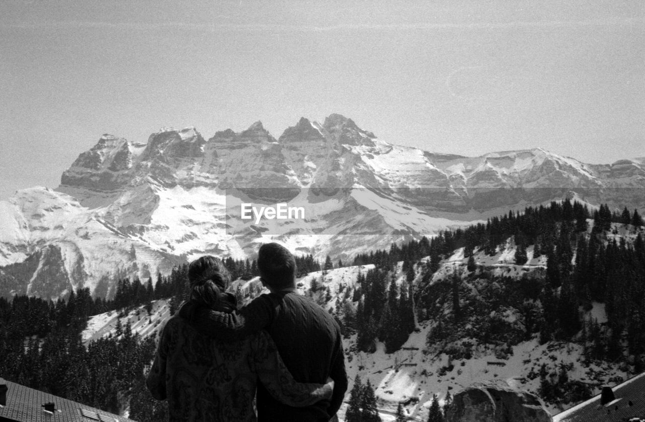 mountain, two people, rear view, mountain range, togetherness, scenics - nature, snow, beauty in nature, women, leisure activity, winter, couple - relationship, adult, men, sky, nature, real people, cold temperature, love, bonding, positive emotion, outdoors, looking at view, warm clothing