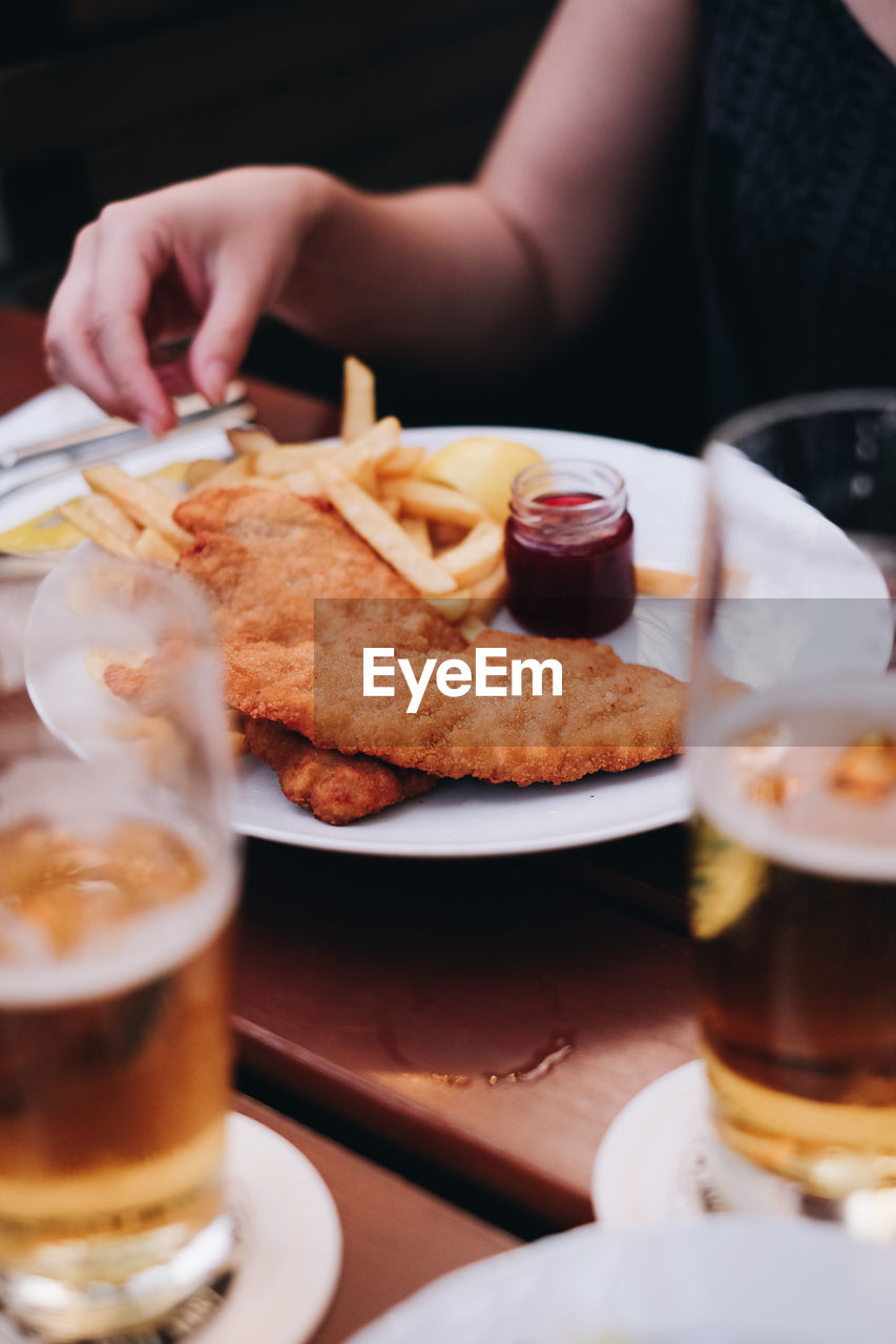 food and drink, food, drink, refreshment, freshness, table, ready-to-eat, human hand, indoors, one person, plate, hand, unhealthy eating, selective focus, human body part, glass, real people, serving size, drinking glass, restaurant, fried, snack, tray