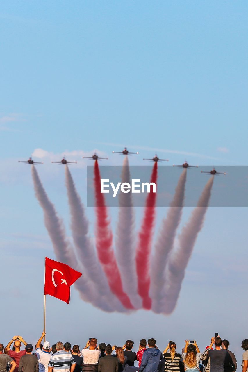 sky, group of people, real people, flag, crowd, large group of people, men, nature, patriotism, flying, clear sky, day, airshow, lifestyles, copy space, women, leisure activity, arts culture and entertainment, outdoors, vapor trail