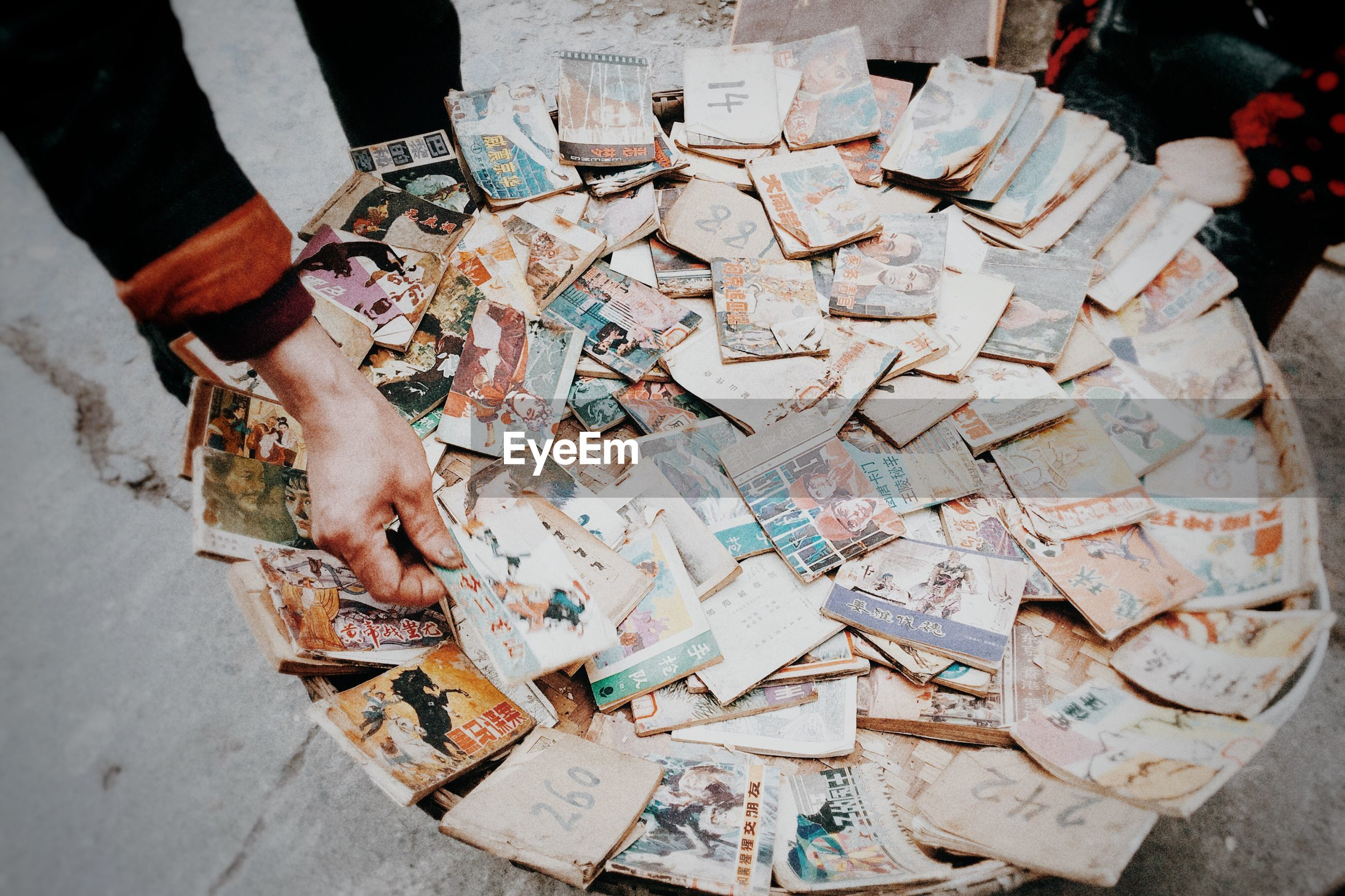 real people, high angle view, paper, lifestyles, religion, text, human body part, men, one person, human hand, paper currency, indoors, day, people