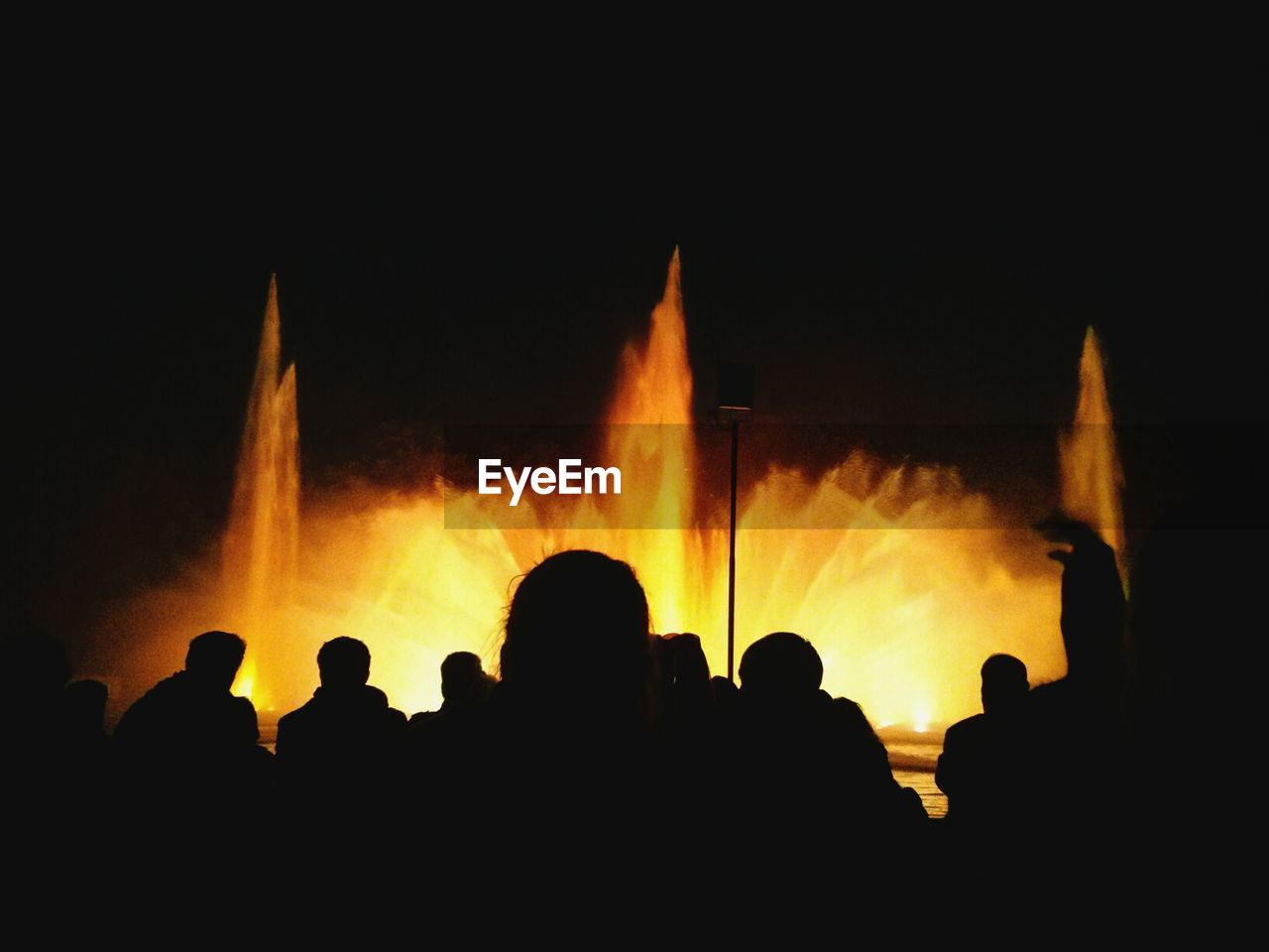 Silhouettes of people by illuminated fountain