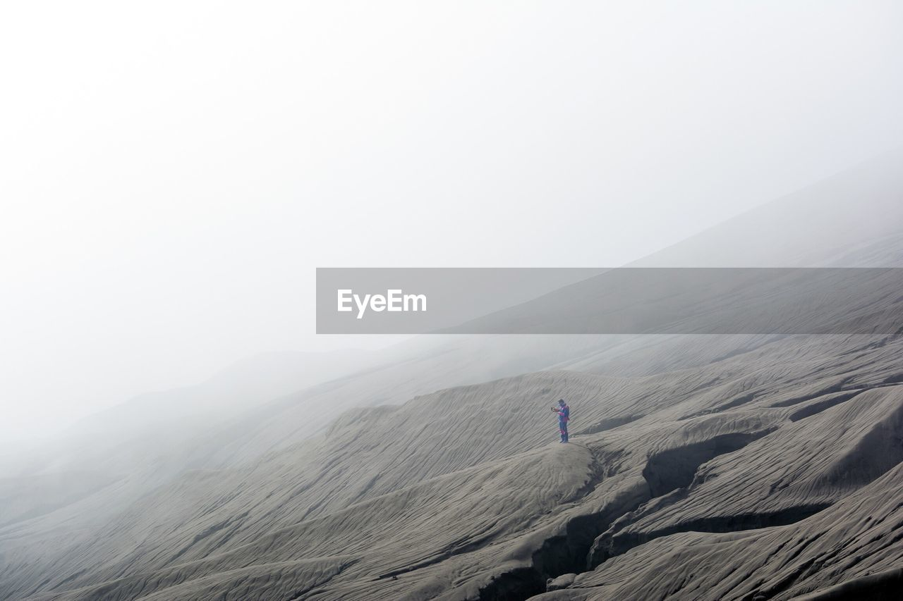 Low Angle View Of Man Standing On Mt Bromo In Foggy Weather Against Sky
