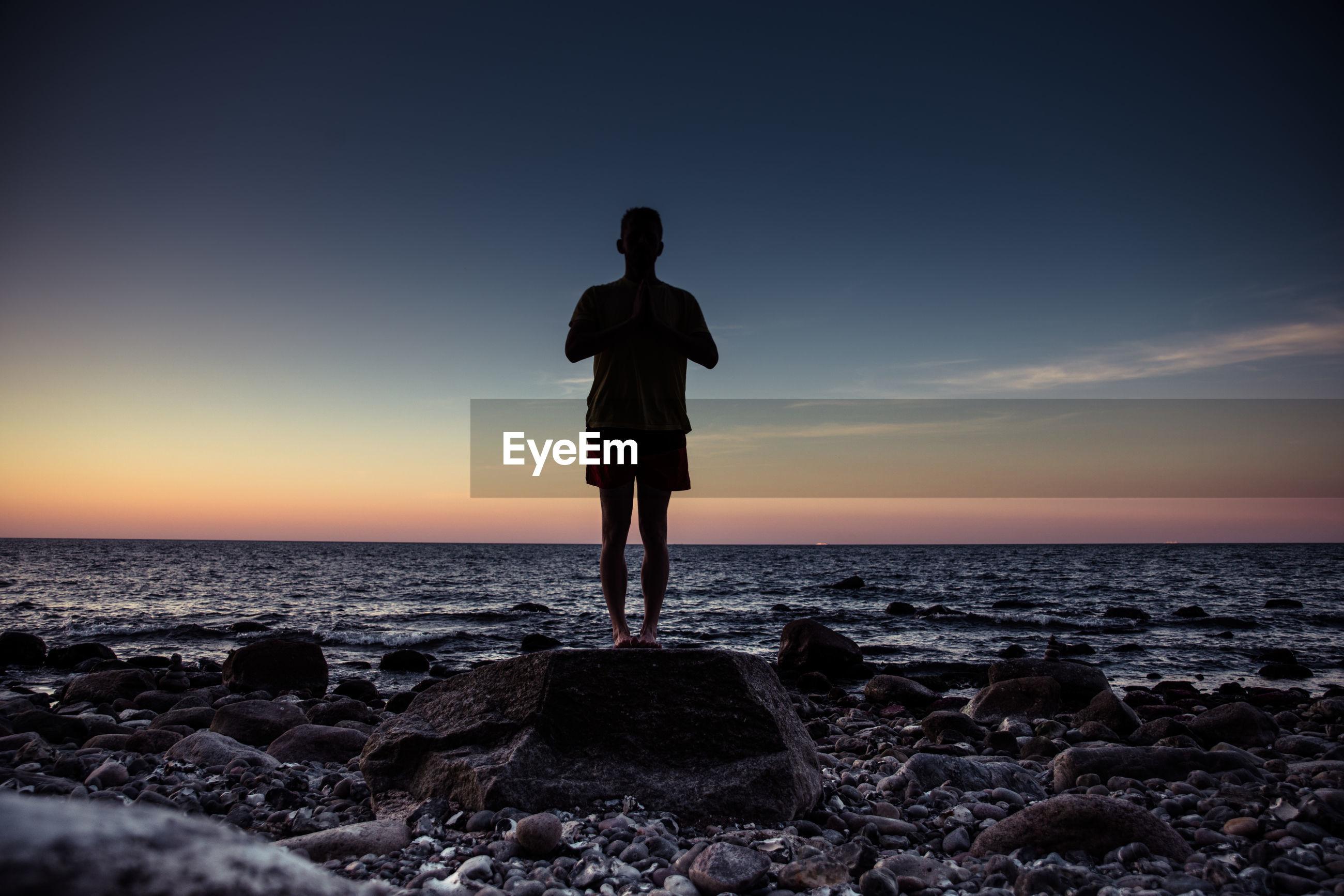Full length of man exercising at beach against sky during sunset