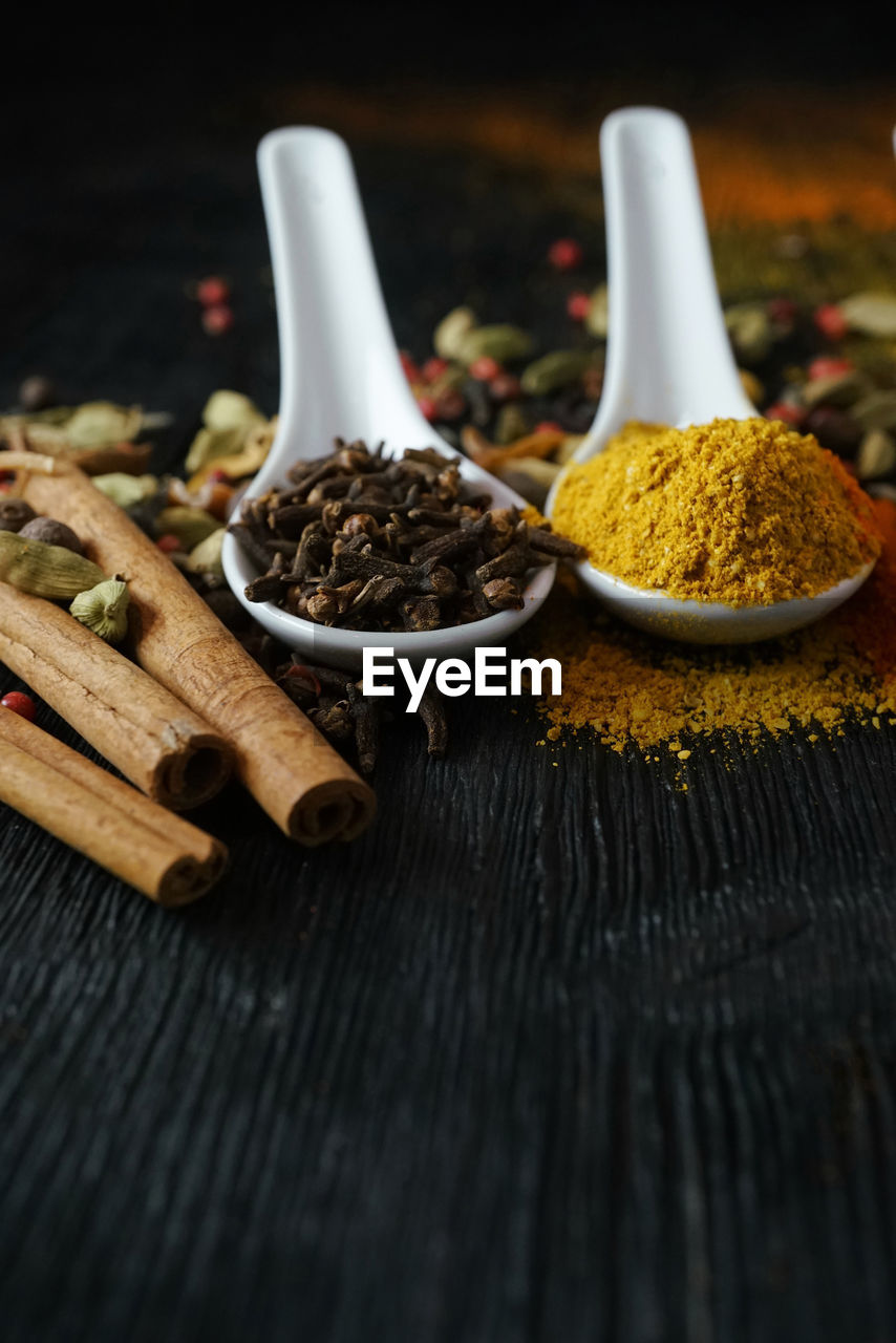 food and drink, spice, food, still life, table, ingredient, wood - material, no people, close-up, indoors, freshness, choice, spoon, variation, kitchen utensil, clove, ground - culinary, cinnamon, eating utensil, high angle view, cardamom