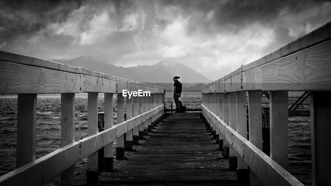 Person standing on pier over sea against cloudy sky