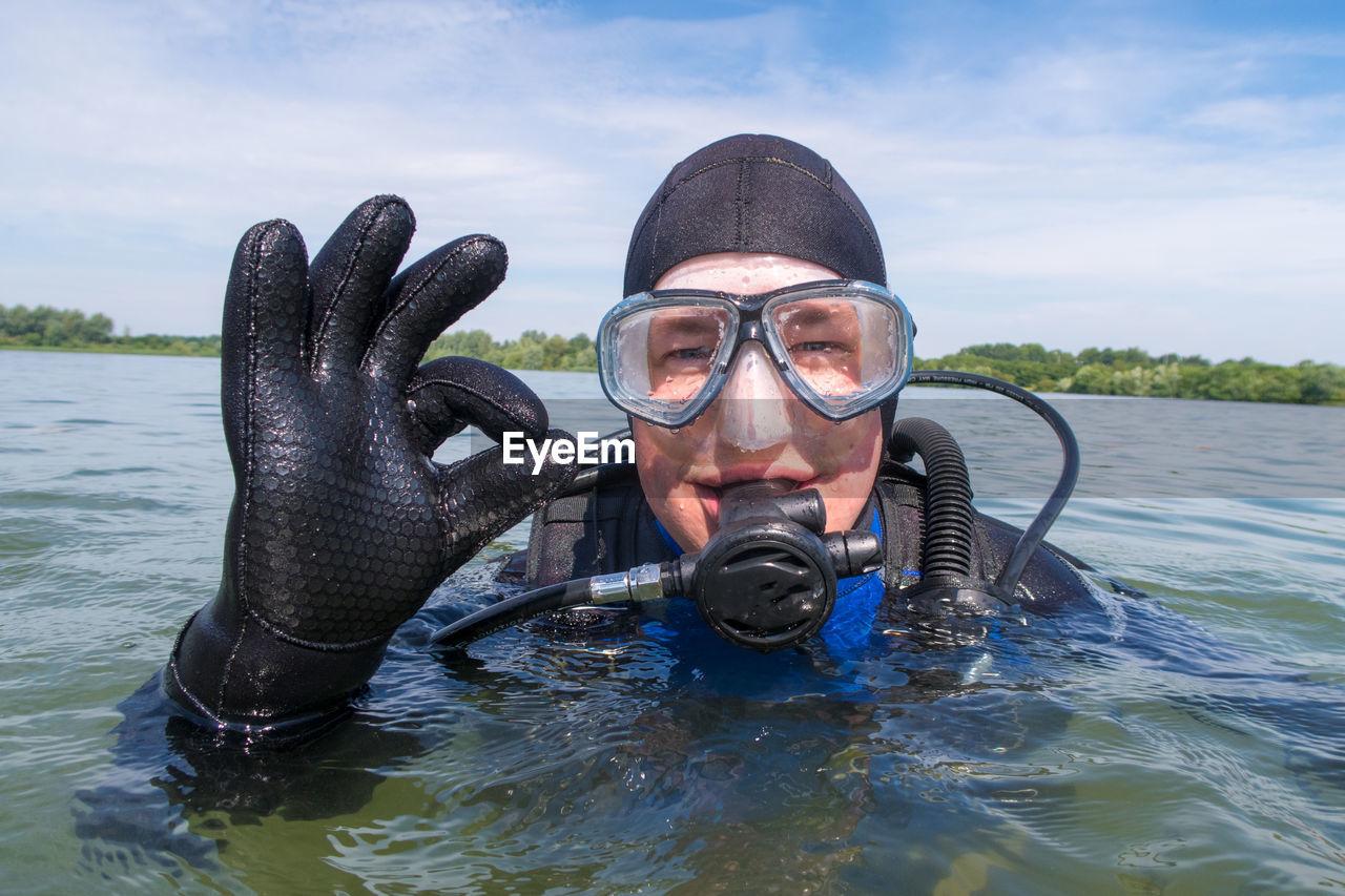 Portrait Of Scuba Diver Showing Ok Sign In Sea Against Sky