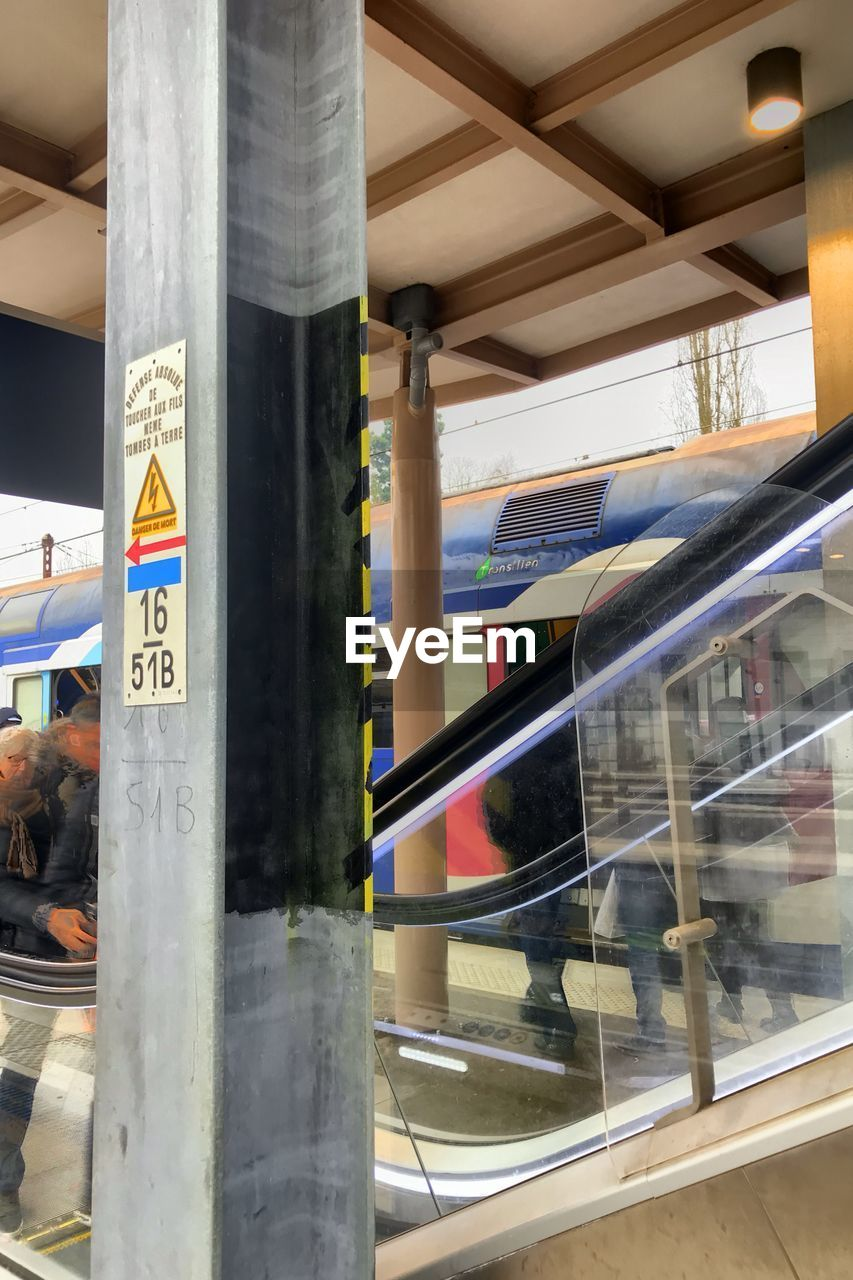 glass - material, transparent, no people, architecture, day, text, public transportation, communication, indoors, built structure, reflection, close-up, focus on foreground, rail transportation, train, mode of transportation, train - vehicle, human representation, architectural column, ceiling
